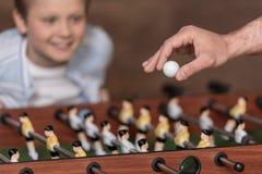 Junge, der Tischfußball und Hand mit Ball im Vordergrund spielt Lizenzfreies Stockbild