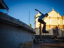 Junge, der Trick in der Luft auf einem Skateboard in einem Park vor einer Kirche durchführt. lizenzfreies stockbild