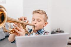 Junge, der Trompete im Wohnzimmer spielend übt stockfotos