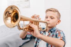 Junge, der Trompete im Wohnzimmer spielend übt stockfoto