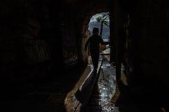 Junge, der in Tunnel im dunklen Kerker läuft Lizenzfreies Stockfoto