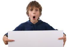 Junge, der unbelegtes weißes Zeichen anhält Lizenzfreie Stockfotos