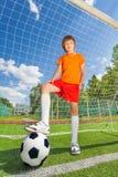 Junge in der Uniform mit dem Bein auf Fußball nahe Holzarbeit Lizenzfreies Stockbild