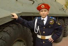 Junge in der Uniform mit einem gepanzerten Truppentransporter Lizenzfreies Stockfoto