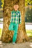 Junge, der unter Baum am Spätsommernachmittag stillsteht Lizenzfreies Stockfoto