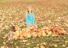 Junge, der unter Blättern sich versteckt Stockfoto