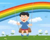 Junge, der unter dem Regenbogen schwingt Stockfotografie
