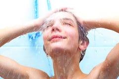 Junge, der unter einer Dusche badet Lizenzfreies Stockbild