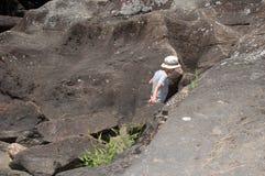 Junge, der unter Felsen klettert Lizenzfreie Stockfotos