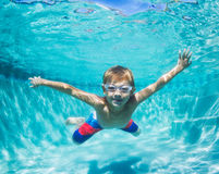 Junge, der unter Wasser im Swimmingpool taucht Stockfoto
