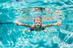 Junge, der unter Wasser im Swimmingpool taucht Stockbilder