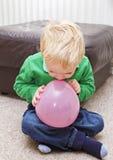 Junge, der versucht, Ballon durchzubrennen Stockfotografie