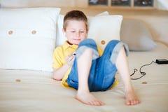 Junge, der Videospiele auf beweglicher Einheit spielt Stockfoto