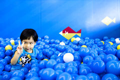 Junge, der voll zwei Finger im Spielzimmer von Bällen anhebt Stockfotografie