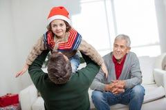 Junge, der vom Vater During Christmas getragen wird Stockbild