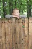 Junge, der von über einem Zaun schaut. Lizenzfreies Stockfoto