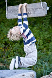 Junge, der von einem Schwingen hängt Stockfotografie