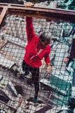 Junge, der von einem sehr hohen Gebäude hängt lizenzfreie stockfotos