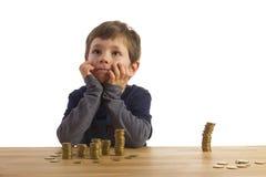 Junge, der vor Geldkontrolltürmen sitzt Lizenzfreies Stockfoto