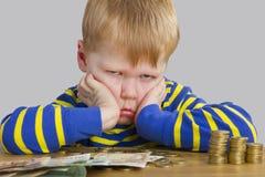 Junge, der vor vielem Geld sitzt Lizenzfreie Stockfotografie