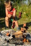 Junge, der Würste grillt lizenzfreie stockfotografie