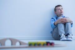 Junge, der an der Wand die Hauptrolle spielt Lizenzfreie Stockbilder