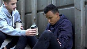 Junge, der warmen Kaffee mit gefrorenem obdachlosem Jugendlichem, Nächstenliebefreiwilliger teilt lizenzfreie stockfotos