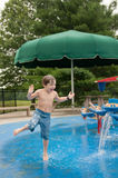 Junge, der am Wasser-Spray-Park spritzt Lizenzfreie Stockfotografie