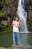 Junge, der am Wasserfall singt Lizenzfreies Stockbild