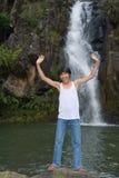 Junge, der am Wasserfall zujubelt Lizenzfreies Stockfoto