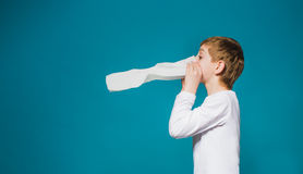 Junge in der weißen Kleidung, die seine Nase durchbrennt Lizenzfreie Stockfotos