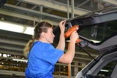 Junge der weibliche Kollektor reparieren ein Detail über ein Autogepäck carri Lizenzfreie Stockfotos