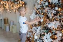 Junge, der Weihnachtsbaum verziert stockfotografie