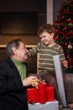 Junge, der Weihnachtsgeschenk vom Großvater erhält Lizenzfreie Stockfotos