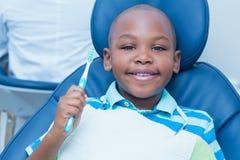 Junge, der Zahnbürste im Zahnarztstuhl hält Stockbild