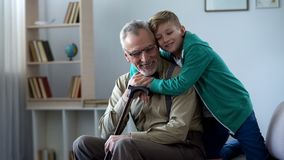 Junge, der zart Großvater, Familienliebe, Respekt für ältere Generation umfasst lizenzfreies stockbild