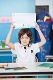 Junge, der Zeichenpapier am Schreibtisch im Kindergarten hält Stockfoto