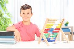 Junge, der zu Hause auf einem Abakus zählt Lizenzfreies Stockbild