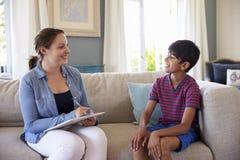 Junge, der zu Hause mit Ratgeber spricht Stockfotografie
