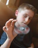 Junge, der zu Hause mit Spinner spielt Stockfotografie