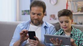 Junge, der zu Hause Tablette, Vaterblättern auf Smartphone, Mangel an Kommunikation verwendet stock video footage