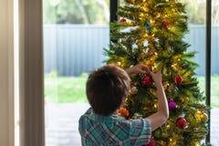 Junge, der zu Hause Weihnachtsbaum verziert stockfotos