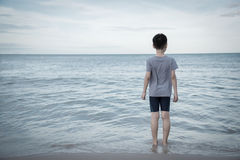 Junge, der zum Ozean schaut Stockfoto