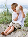Junge, der zum Seashell am Strand hört Lizenzfreie Stockbilder