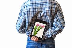 Junge, der zurück Tablet-Computer hinter seinem hält Lizenzfreie Stockfotos