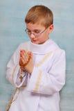 Junge, der zur ersten heiligen Kommunion mit einem Rosenbeet geht stockfotos