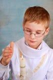 Junge, der zur ersten heiligen Kommunion mit Kerze geht Stockbild