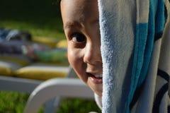 Junge, der zur Kamera nach einem netten Bad in einem Swimmingpool lächelt Lizenzfreies Stockbild