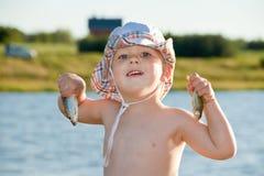 Junge, der zwei kleine Fische hält stockfotos