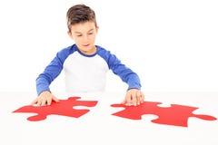 Junge, der zwei sehr groß Stücke eines Puzzlespiels anschließt Stockbild